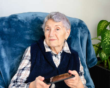 A senior woman holding a smartphone in her hand