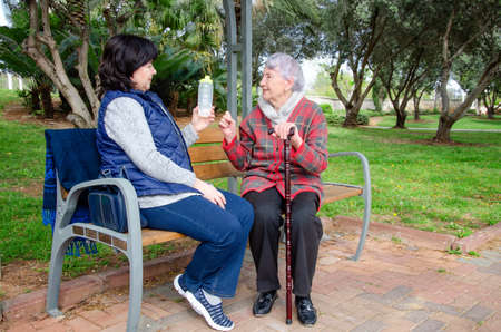A caregiver with an older woman on a bench