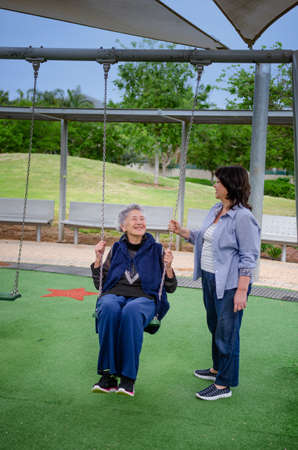 Grey-haired senior woman likes a baby while a female caregiver or caring daughter pushing her on a swing.