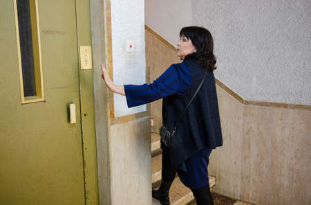 Mature woman rejects a lift and walks upstairs in a residential house. Stock Photo