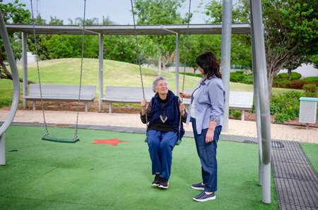 Black haired caregiver assists elderly woman swinging on a swing set. Caring for aging people is her job.