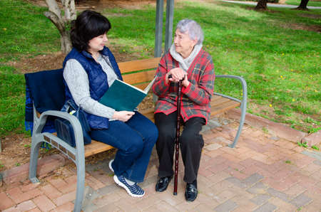 Older woman loves the female caregiver reading a book out loud for her.