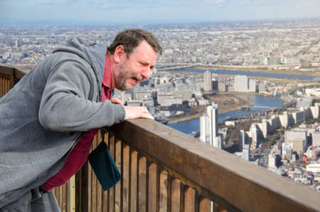 A mature man is afraid of heights. He stands on the observation deck and looks down at the panoramic view of the big city. This man is very scared. He suffers from acrophobia.