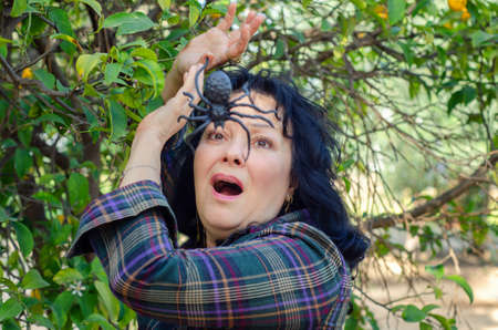 The arachnophobia victim woman experiences a panic attack at the sight of a big ugly black spider in front of her face Stock Photo