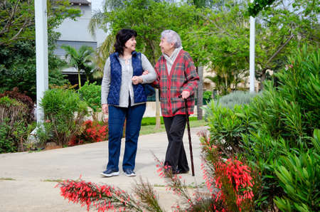 Female volunteer helping an elderly woman to walk in the city park. Stock Photo