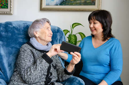 Female caregiver or volunteer came home to an elderly lady to teach her how to use a smartphone.