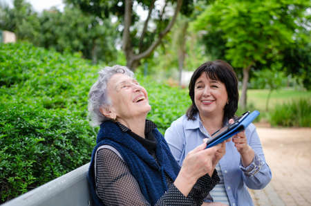 Mature female caregiver teaching an elderly woman how to use a tablet. They are really happy with her first successes. Women sit on a park bench.