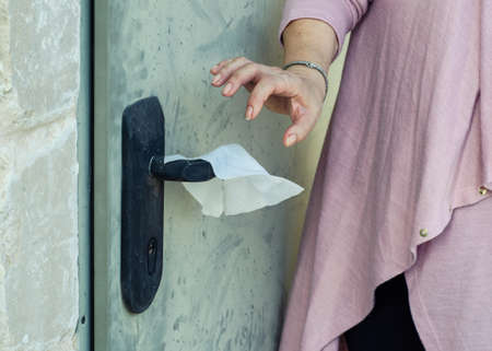 Woman is afraid to get corona virus. She tries to open the door with the help of a hygiene napkin but not in gloves.