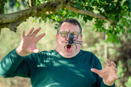 Middle-aged man undergoes a panic attack encountering a spider when strolling in the garden.