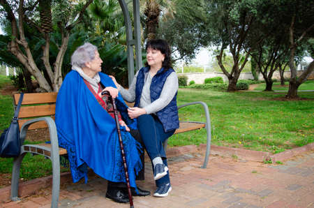 Mature female home helper and a senior woman talk sitting on a bench in a city park. Stock Photo