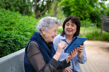Caring daughter or mature female volunteer teaching her elderly mother or an older woman how to use a tablet. Two women sit on a bench in a city park.