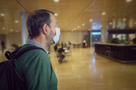 Slightly confused man in a face mask looking around in a half-empty airport departure lounge. Stock Photo