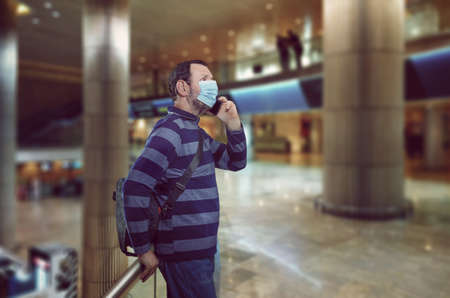 A middle-aged man in a face protective mask is talking on a cell phone leaning on a railing in a half-empty airport.