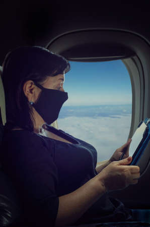 A mature woman in a protective mask is flying by plane during the pandemic. She is reading something on the tablet. Night shot on the window background.