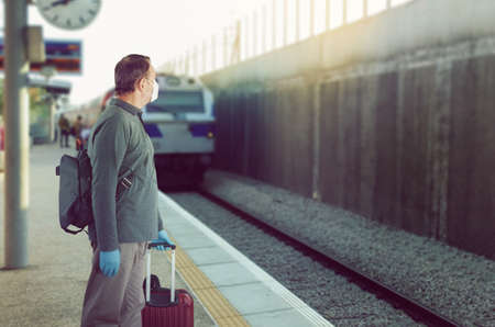 Man in a medical mask and blue rubber gloves is waiting for a train. He stands on the platform with baggage.