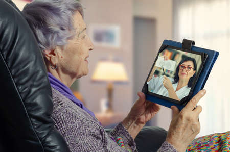 An elderly lady sits at home in a leather chair and holds a tablet in her hands. She carefully looks at the telemedicine doctor on the screen.