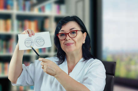 Middle-aged friendly eye doctor in white uniform looking at the camera. She shows a diagram of the normal field of view (FOV).  Woman has black hair and wears glasses.