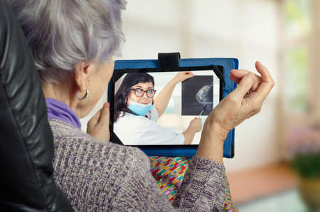 Telemedicine doctor in white uniform and blue face protective mask explains to a geriatric patient the importance of breast cancer screening.