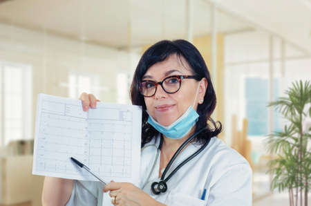 Attentive female cardiologist points out the printed treadmill test graph in her hands looking at the camera. The mature woman wears white uniform and blue protected mask. Stock Photo