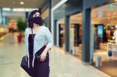 Adult woman in a black mask glances at the storefronts while walking through an airport. She rolls a big black suitcase on wheels.