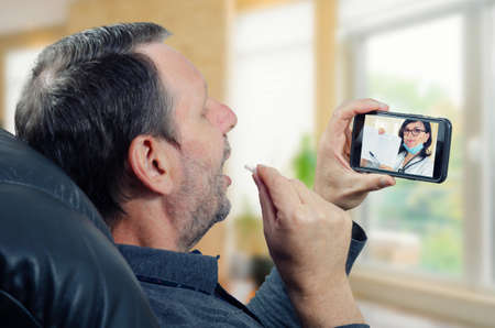 Telemedicine doctor communicating with the remote male patient about the results of his exercise tolerance test (ETT). The man takes a pill during telecommunication.