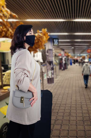 Middle-aged woman in a gray cardigan in a black face mask has just arrived at an airport or train station. She holds a large black suitcase at the left side.