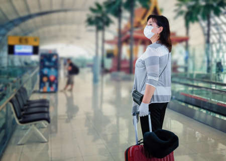 The woman in the white mask stopped for a second at the airport. She carefully examines the interior.