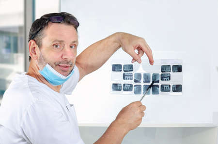 Cordial dental surgeon in white uniform showing dental X-rays Stock Photo