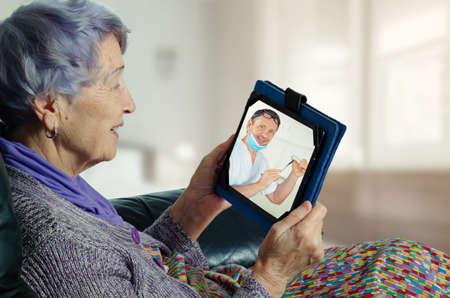 Telemedicine dental surgeon explains to an elderly female patient the details of the coming implantation.