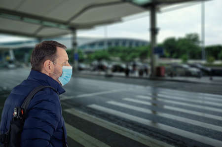 Mature man in blue face mask retires from an airport building on a wet day.