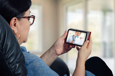 Middle-aged woman is really interested to listen to telemedicine doctor using a mobile phone application. Stock Photo