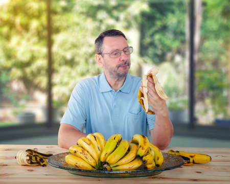 Having learned about the health benefits of bananas for seniors, a bearded man decided to eat them every day Stock Photo