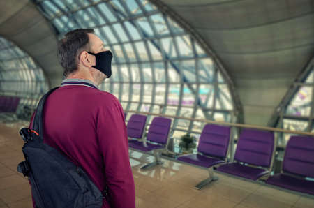 Mature man in a black face mask scrutinizes the interior design of an unfilled airport.