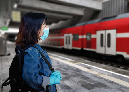 Black haired woman in a blue mask and gloves is watching for a train on a platform Stock Photo