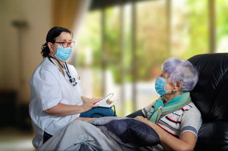 The doctor gerontologist visited a senior woman patient during a pandemic to take blood pressure. Now they are sitting and talking. This is very important for single elderly people. Stock Photo