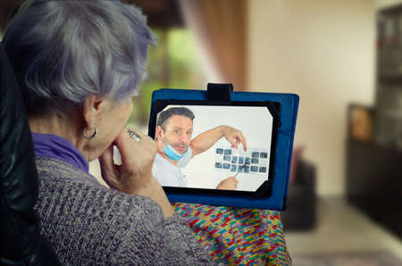 Telemedicine dentist explains to an elderly remote patient which teeth need treatment urgently.