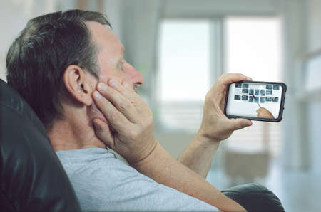 Dental clinic shows x-rays images to a remote patient on his mobile phone using a telemedicine application Stock Photo