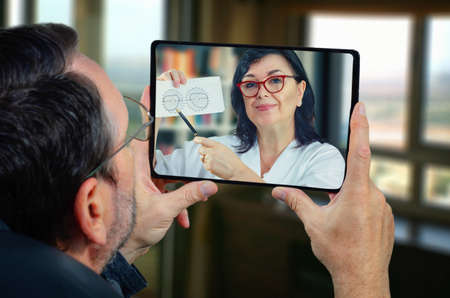 Mature man sits at home holding a tablet in his hands. He carefully looks at the telemedicine doctor on the touch screen. GP recommends his taking field of view (FOV) test as soon as possible. Stock Photo