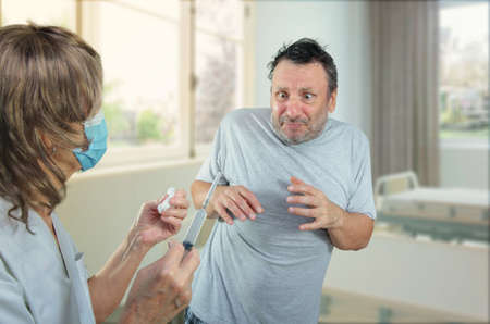 Man in a hospital recognized that the nurse would give him an injection and panicked. He is scared to death. Stock Photo