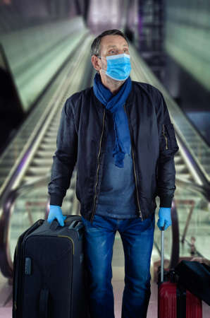 Mature man wearing a protective mask and gloves came down the subway with his luggage