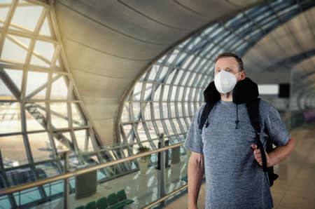 Middle-aged passenger with a backpack wears a white protective mask in the airport terminal Stock Photo