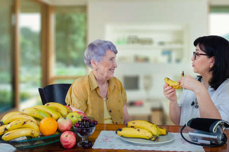 On the advice of a doctor geriatric, a senior adult woman began to eat bananas every day. As a result, her blood pressure is back to normal. Stock Photo