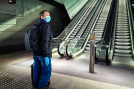 Mature traveler in a protective mask and gloves looks around near the subway escalator on an empty platform.