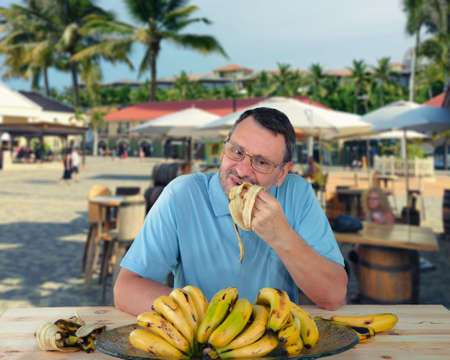 Mature man is eating bananas in large quantities while roving in tropical countries. He wants to fill his body up with potassium. Stock Photo