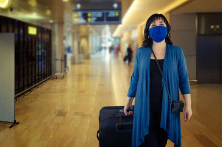 Woman in navy clothes and a protective mask of the same color moves out of an airport arrivals terminal with a black suitcase on wheels. Stock Photo