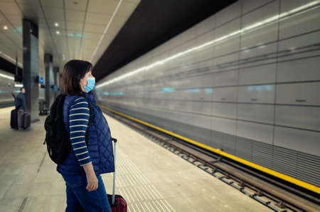A black-haired, middle-aged traveling woman in a protective blue mask waits for a train on a subway platform. She has luggage.