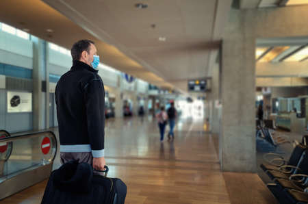 Traveling man in a blue protective mask entered an airport or train station Stock Photo