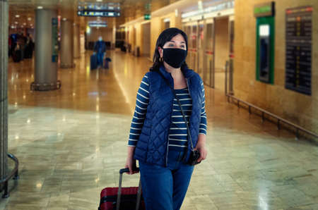 Woman in a black protective face mask goes through the arrival or departure hall of an airport. She is dressed in dark blue clothes and rolls a suitcase on wheels.