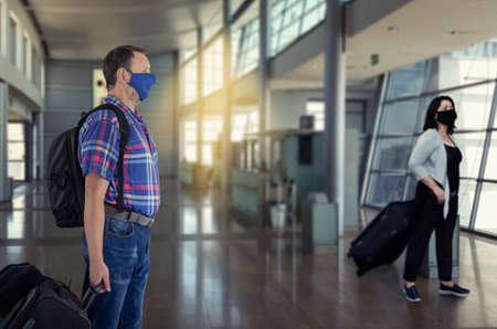 Man and woman in protective masks hurries to a check-in terminal of an airport Stock Photo