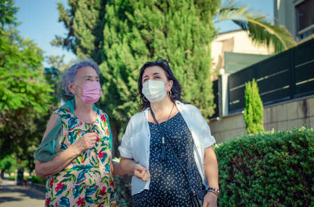 Caregiver or nurse and a senior adult woman stroll in a green street during coronavirus. Both are wearing face protective masks.